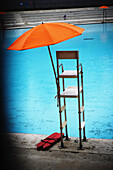 Orange umbrella on top a lifeguards stand overlooking a swimming pool in Central Park, Manhattan, New York City, New York.