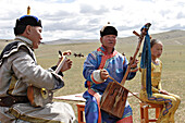 Mongol musicians, perform 'Khoomii' or throat singing a 'Urtyn Duu' or long epic song, and play 'Morin Khuur'  a horse headed string instrument which are unique and most popular in Mongolia.  Annual Naadam festival, Kharakhorin, Central Monglia.