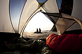 Maren Ludwig and Brad Hill watching the sunset while camping at Hug Point on the Oregon Coast.