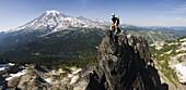 Climber Ian Derrington enjoys the views of Mount Rainier from the narrow summit of Castle Peak on a traverse of the Tatoosh Range in Mount Rainier National Park, Washington.