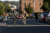 A young man and woman smile as they ride their bikes up a busy street on a sunny afternoon in Portland, ME.