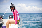 THATCH CAYE, BELIZE. A woman sits on the edge of a boat before snorkeling in the clear waters of the Caribbean.