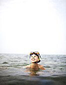 Ambergris Cay, Belize. A woman smiles with a snorkel and mask on her head.
