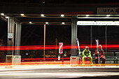 Two men wait for public transportation in Salt Lake City after a day of skiing, Utah.