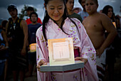 An Asian woman smiles as she looks down at her lantern while waiting to participate in the Lantern Floating Hawaii Ceremony on May 25th, 2009 at Magic Island in Honolulu, Hawaii. The ceremony is an Asian spiritual tradition that symbolizes the wish for al