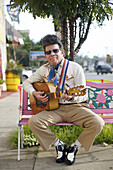 'Raphael ''Elvis'' Coca, originally of San Salvador, sits outside the La Parilla restaurant where he works, in Silver Lake, Calif., on Sunday, Jan. 31, 2010. He works in the restaurant as a performer.'