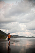 DOMINICAL, COSTA RICA. A man walks down the beach with his surfboard at dusk beneath a cloudy sky.