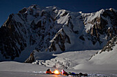 A very cold winter night out beneath the huge and imposing Brenva Face of Mont Blanc. Priming a petrol stove to start cooking food,  Chamonix France