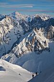 Two ski tourers climb up the final snow arete to the Aiguille du Midi,  Chamonix France