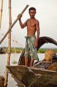 Srimangal,  Bangladesh - July 2011:  Bangladeshi man living and fishing on a small boat in a seasonally flooded area near Srimangal,  Bangladesh.