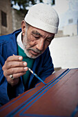 Portrait of a senior man hand painting one of his handmade crafts, Chefchaouen, Morocco