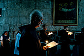 Monk and a nun pray by candlelight in the Church of the Holy Sepulchre