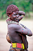 Hamar women adorn their necks with heavy polished iron jewelry and roll their locks with fat and red ochre assile, and than twist them into crimson-colored dreads called Goscha, a style that men find attractive.  Dimeka, Ethiopia, 2010  Dimeka, Omo Valley