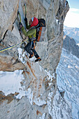 Seconding with a heavy pack high up on the cruxes of No Siesta on the Grandes Jorasses north face, Chamonix. This route is thought of as one of the hardest in the Alps, and takes 3 days on the face itself.
