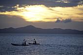 Sea Kayakers explore the Coron Islands at sunset, Palawan Islands, Phillippines. Photo by Greg Von Doersten/Aurora