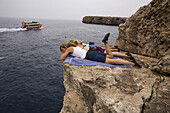 Kim Miller, Catherine Brunel-Guitton and Melissa Lacasse sun themselves and watch climbers deep water soloing on the wall below while waiting for their turn to deep water solo in Cala Sa Nau, Spain.