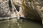 Whit Richardson submerged in pool of nasty water holding pack above his head and water while descending Miners Hollow or Knotted Rope Canyon, San Rafael Swell, Utah.  Whit Richardson / Aurora Photos