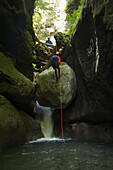 Davis Creek, South of Mount Rainier, WA. Canyoning is a new sport that consists in travelling down river canyons by walking, gliding, climbing, rappelling abseiling, swimming or jumping. Joe Budgen red, rappels abseils, down past a Indiana Jones like boul