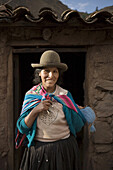 PISAC, PERU - AUGUST 16:  A Quechua woman is photographed in front of a rustic local bar in Pisac, Peru on August 16, 2006. Photo by Dennis Drenner/Aurora