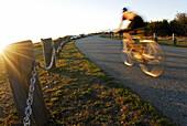 Dana Lis cycling at sunset at Iona Beach in Richmond, British Columbia, Canada.