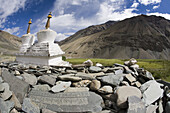 Buddhist chortens or stupas and mani stones lie in green valley, Zanskar Mountains, Ladakh, northern India.  This predominantly Buddhist area  is near the border with Tibet, China.