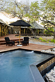 An infinity pool and lounge chairs under the canopy of shade at Onguma tented camp on the Onguma Private Nature Reserve, Etosha National Park - Namutoni Gate.