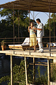 A young couple drinking wine on the deck overlooking a river in Carmelo, Uruguay.  releasecode: THS_0011, THS_0012