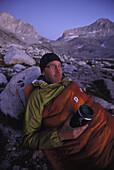 Dan Duane enjoying a hot drink in his sleeping bag while on a backpacking trip on the Sierra High Route, a 195 mile trackless path almost entirely between 9,000 and 11,500 feet in elevation in the Eastern Sierra Nevada mountains in California.