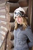 Beautiful Andrejka stands in the doorway of her log house.  With her goggles on she's ready to go snowboarding, Sandpoint Idaho