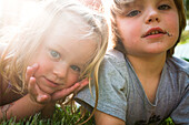 Two small kids smile for the camera in the garden. releasecode: sloan_cordon, kieran_reilly