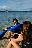 Michelle Cove and Dylan Murray relax in shallow water in preparation for a beach dive, New Providence, Bahamas