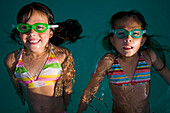 Two girls in goggles float in the water at a pool party.