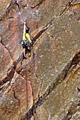 'Craig DeMartino; a climbing accident amputee, rock climbing in Eldorado Canyon State Park, doing the route, Werk Supp 5.9 near Boulder, Colorado.'