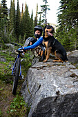 Sol Mountain, BC - Kate Watters and her dog, Babushka, rest as they mountain bike across alpine meadow while flowers in bloom at Sol Mountain Touring's backcountry lodge in the Southern Monashee range of the Columbia Mountains of South Central British Col