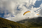 ROSELAND PASS, SAVOIE, FRANCE-SEPTEMBER 11, 2007: Three paragliders soaring through the air on a cloudy day near Roseland Pass in Savoie, France on September 11, 2007.