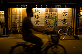 A man quickly rides his bicycle down the street in Tokyo, Japan. Cycling is a popular mode of transportation in Japan.
