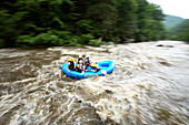 Zoom blur image of unknown rafters running the Cheoah River near Robbinsville, NC. This river was only recently opened to whitewater enthusiasts and only runs a few days each spring and fall when the gates at Santeetalh Dam are opened.