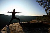 Sarah Chouinard enjoys a late afternoon yoga session pose : Warrior II - virabhadrasana, atop the Bosnian Buttress along the rim of the New River Gorge near Fayetteville, WV