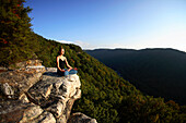 Sarah Chouinard enjoys a late afternoon yoga session pose : Tree - vriksha asana, atop the Bosnian Buttress along the rim of the New River Gorge near Fayetteville, WV