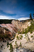 The grand canyon of the Yellowstone River in Yellowstone National Park, Wyoming is starkly majestic with pink rock and thick clouds overhead on July 22, 2005.