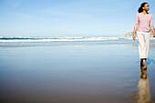 An African-American woman enjoys a morning walk on a beautiful California beach.