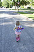 Della Rose Wheatcroft walks down the street with her doll and pink cowboy boots on. The image illustrates the wonder of childhood, imagination, and the innocence of being a kid. Sandpoint, Idaho.