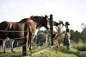 Della Rose Wheatcroft and Ahlya Lizotte feed two horses on a rural farm near Eugene, Oregon.