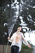 A woman squirts water from a hose into the air as she stands under the falling water, San Diego, California. model release code: gibbs_carolyn.jpg