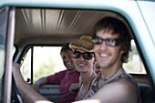 A group of friends sit in the front seat of an old truck. All three people are looking at the camera smiling but only one is in focus. Sandpoint, Idaho. Kevin Battey,Kristine Battey, and Woods Wheatcroft.