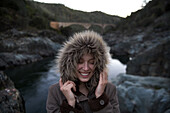A woman smiles holding the fur of the hood of her jacket in front of a river, Auburn, California.