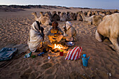 Camel herders gather for breakfast tea as they travel through the Sahara desert, Sudan on a camel caravan.