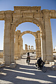 Palmyra, Syria - January, 2008: Motor bikers take a shortcut through Roman ruins in the desert.  Palmyra or Tadmore was a 2nd century AD desert oasis used as a strategic staging post for caravans traveling between the Mediterranean Sea and the east.  It w