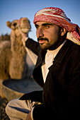 Palmyra, Syria - January, 2008: Portrait of a young Syrian Bedouin  man with his camel in the desert.
