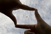 An airplane framed by 'cinema' fingers.